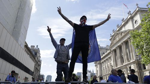 Members of Football Lads Alliance, standing at a police barrier along Whitehall, in central London, chant slogans, Saturday, June 13, 2020