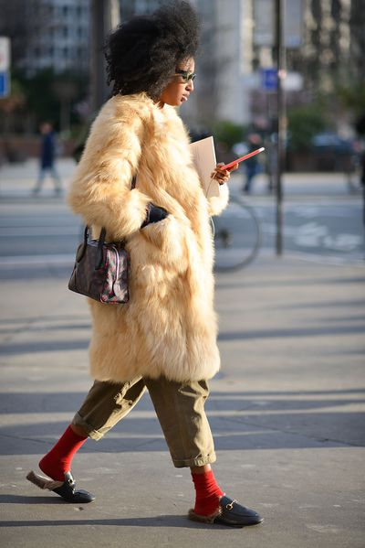 Julia Sarr Jamois pairs the omnipresent fur-lined Gucci loafers with red socks and a fur chubby.
