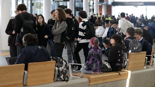 Commuters wait for transport at a bus interchange in Christchurch, New Zealand, Monday, June 8, 2020. (AP Photo/Mark Baker)