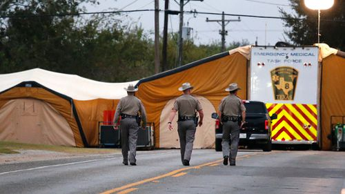 Three Texas State Troopers walk up the street to the command tents. (AAP)