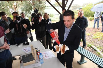 Victorian Opposition Leader Matthew Guy saucing up a democracy sausage on the final day of the Victorian election campaign.