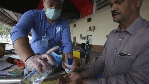 A Pakistani volunteer helps a passenger arriving at a railway station to wash hands as a measure to help prevent the spread of the coronavirus.