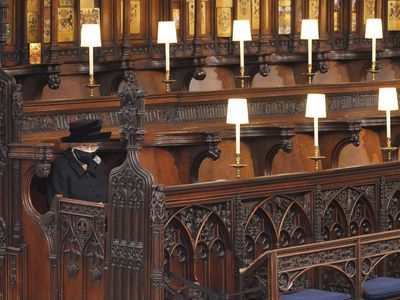 Queen Elizabeth II sits alone during her husband's funeral service