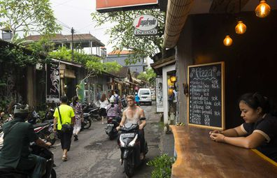 Ubud, Bali - February 12, 2017: Pedestrians and people on scooters move down a street lined with shops and restaurants in Ubud, Bali.