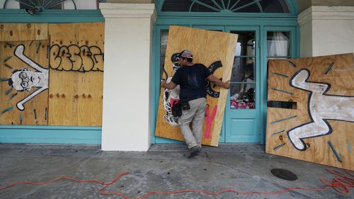 In preparation of Hurricane Ida, a workers attach protective plywood to windows and doors of a business in the French Quarter in New Orleans, Saturday, August 28, 2021. (AP Photo/Eric Gay)