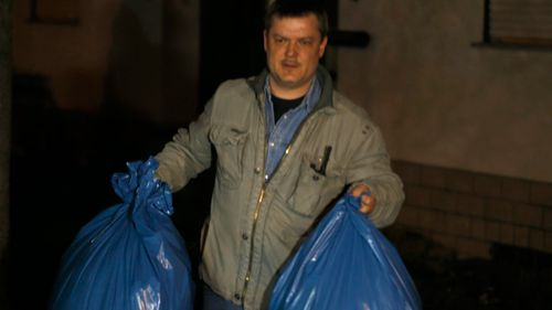 An investigator carries bags from the home of the family of Andreas Lubitz. (AAP)