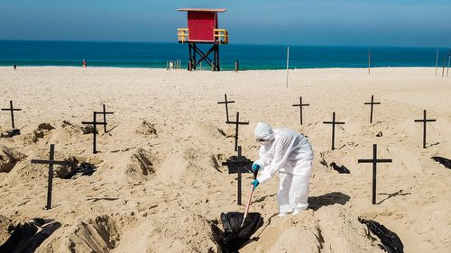 Protesters from the NGO 'Rio De Paz' dig symbolic graves as a sign of protest in Copacabana beach in Rio de Janeiro, Brazil. Volunteers dug 100 shallow graves symbolising the deaths of coronavirus in the country. The act calls for transparency and an attitude change from the government to fight the pandemic.