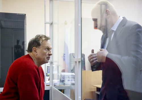 Oleg Sokolov, a history professor at St. Petersburg State University, left, listens to his lawyer sitting in a cage waiting for a court session in St. Petersburg, Russia