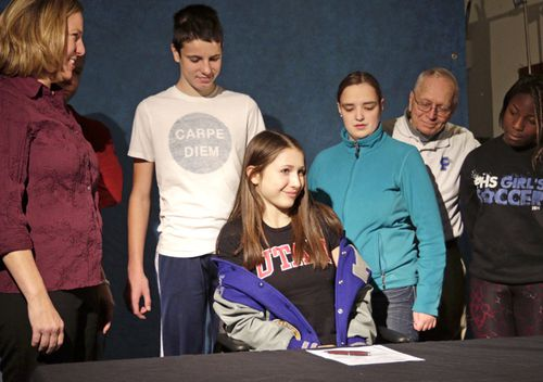 In this 2014 photo, then Pullman High School senior Lauren McCluskey is surrounded by her family before signing a letter of intent to compete in track for the University of Utah. McCluskey was shot and killed outside of a University of Utah dormitory on campus in Salt Lake City.