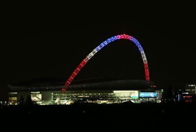 The famous arc of Wembley Stadium lights up in the French colours.