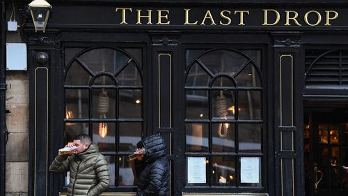 Members of the public enjoy a drink at the Last Drop pub in the Grassmarket prior to last orders at 6pm on October 9, 2020 in Edinburgh, Scotland.