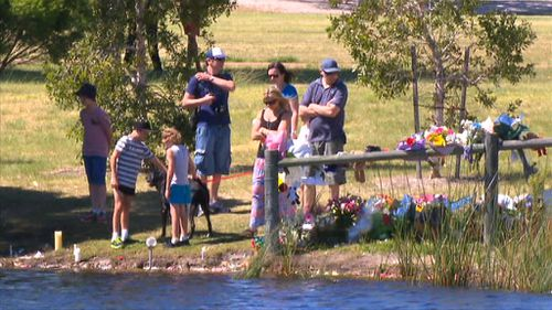The Trott family visited the lake where Sam was found, taking time to read messages left for them. (9NEWS)