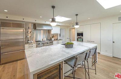 The chef's kitchen impresses with a flood of natural light (thanks to the skylight) along with a huge marble island and stainless steel appliances.