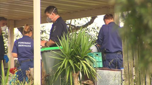 Forensic officers document the crime scene at which a 35-year-old man was fatally stabbed.