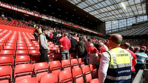 Security escort fans from their seats at Old Trafford. (AAP)