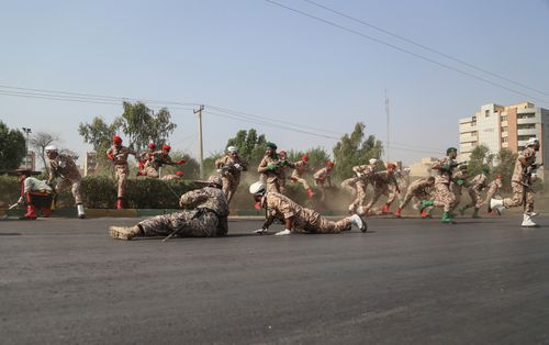 Iranian soldiers, women, and children lay down and run during a terror attack that occurred at military parade in the city of Ahvaz, southern Iran. (AAP)