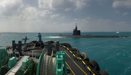 A US Navy Los Angeles class submarine surfaces along side a Japanese navy resupply vessel during the Keen Sword drills. (US Navy).