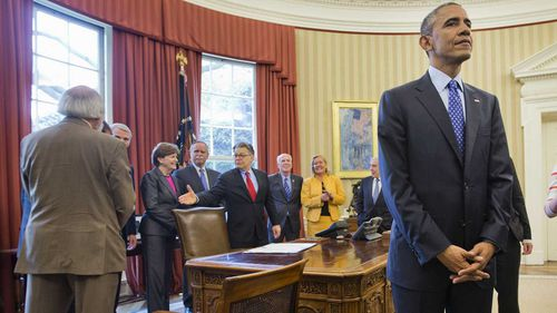 Al Franken (centre) in the Oval Office with then-president Barack Obama. (AAP)
