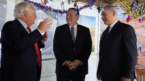 U.S. Secretary of State Mike Pompeo, center, Israeli Prime Minister Benjamin Netanyahu, right, and U.S. Ambassador to Israel David Friedman speak at a sukkah, a traditional shack built for the weeklong Jewish holiday of Sukkot