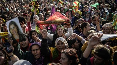 Kurdish people hold a picture of fighter during a celebration rally near the Turkish-Syrian border at Suruc, in Sanliurfa province, who was killed in conflict with Islamic state militants in Kobani.