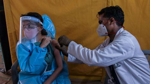 A young woman gets a coronavirus vaccine in New Delhi, India.