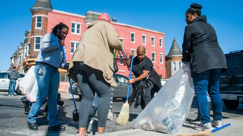 Volunteers clean up rubbish and shattered glass in front of a looted business in Baltimore. (AAP)
