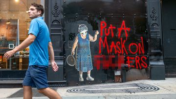A man in New York City without a mask walks past street art with a message urging people to wear face masks to stop the spread of coronavirus.