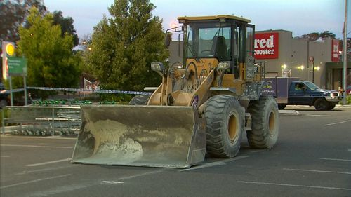The tractor was used to break the glass shopfront, before dislodging two ATMs. (9NEWS)