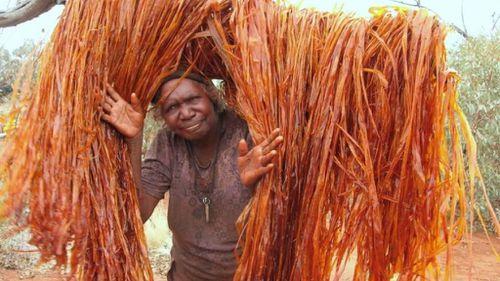 Tjanpi Desert Weaver, Ivy Laidlaw, working to create artwork using bush-dyed raffia. (Tjanpi Desert Weavers)