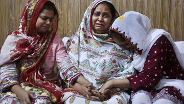 Family members of an air hostess Anam Maqsood, who was killed in Friday's plane crash, mourn for her death at their home in Lahore, Pakistan, Saturday, May 23, 2020