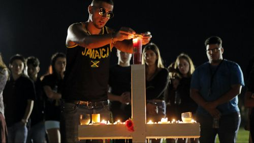 Joey Kandil, 18, a recent graduate of Marjory Stoneman Douglas High School, places a ring around a candle on one of seventeen crosses, after a candlelight vigil for the victims of the Wednesday shooting at the school. (AAP)