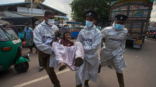 Sri Lankan police officials detain a man who violated the COVID-19 guidelines imposed by the authorities to curb the spread of the coronavirus in Colombo.