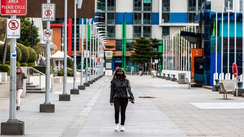 A lone pedestrian walks along a street in the Docklands precinct on September 25, 2020 in Melbourne, Australia.
