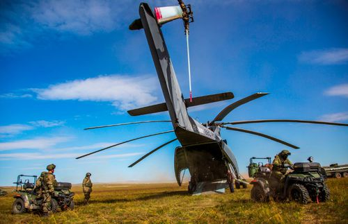 Quad bike-riding soldiers leave a  Russian Mi-26 helicopter in the Vostok 2018 exercises.
