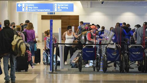 Passengers gather at Orlando International Airport in Florida today.