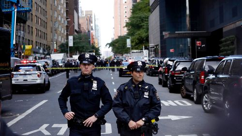 Police stand guard in a closed street after a bomb alert at the Time Warner offices in New York.