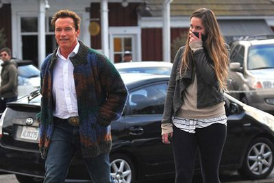 Arnie's swapped muscles for old man fashion, and daughter Christina just can't contain her giggles!