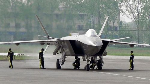 Chinese ground crew members inspect a J-20 stealth fighter in Chengdu, in southwest China's Sichuan province.