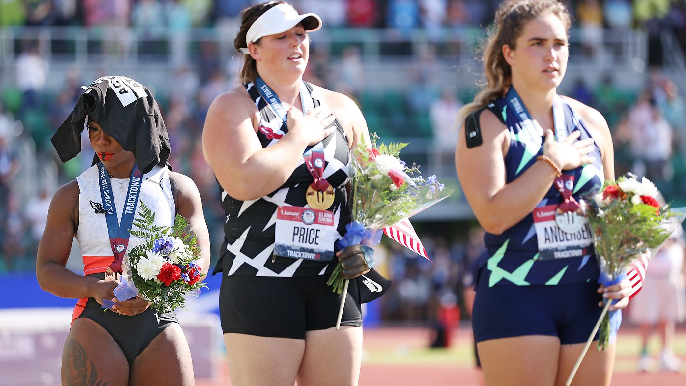 Gwendolyn Berry (L), third place, looks on during the playing of the national anthem with DeAnna Price (C), first place, and Brooke Andersen, second place, on the podium