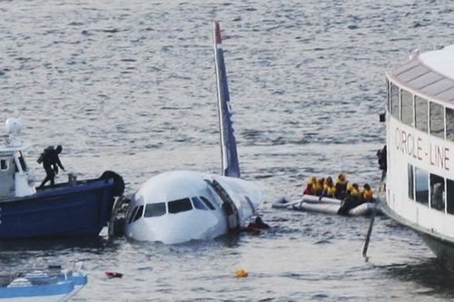 A diver (left) aboard an NYPD vessel prepares to rescue passengers of the US Airways plane that landed on the Hudson River.