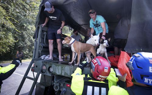 New York Urban Search and Rescue team members help residents get off of a truck after being evacuated.