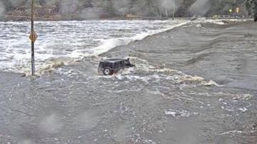 Concerns for driver who tried crossing flooded road in half-submerged car