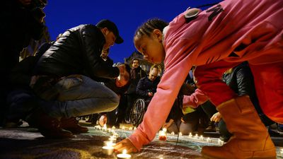 Members of the public gather at the Place de la Bourse in Brussels to leave messages and tributes following the terrorist bomb attacks. (AAP)
