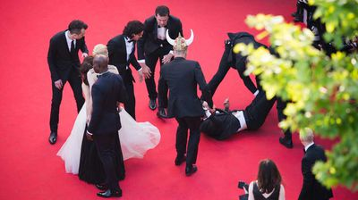 The intruder is dragged away from the cast. (Getty)