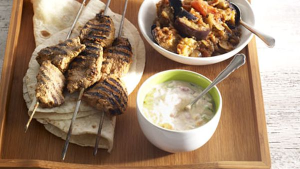 Lamb tikka kebabs with spiced eggplant, tomato raita and cucumber salad