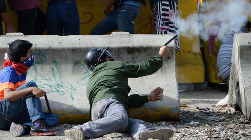 An anti-government activist fires an improvised handgun made out of an iron tube which can fire a marble or a steel ball bearing. (AFP)