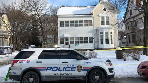 Police secure the perimeter of a home in Troy, N.Y., after four bodies were discovered in a basement apartment. Troy police say the deaths are being treated as suspicious. (Nicholas Buonanno/The Record via AP)