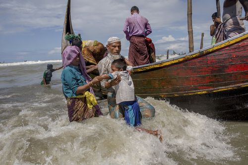 An elderly Rohingya Muslim man helps a boy get off a boat after they arrived from Myanmar to Bangladesh in Shah Porir Dwip. (AP)
