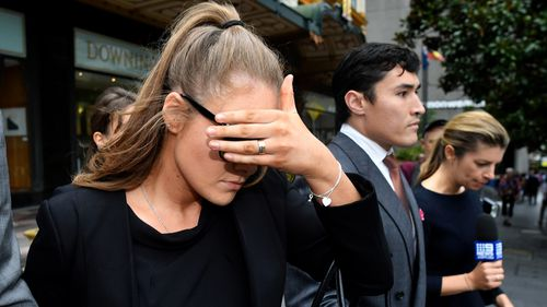 Sarah Jane Chisholm Rogers, 24, covers her face as she leaves court in Sydney.
