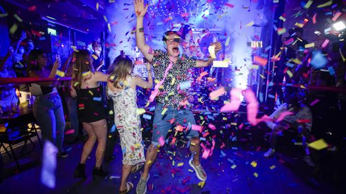 A man jumps on the dance floor shortly after the reopening of The Piano Works Farringdon in London, as England's country's nightclubs reopened.